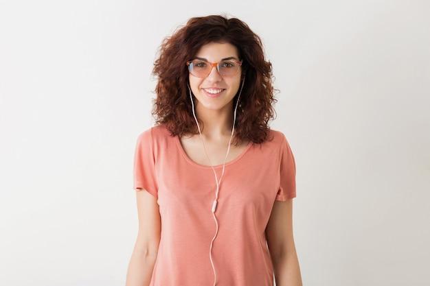 Giovane donna abbastanza elegante in occhiali ascoltando musica su auricolari, capelli ricci, sorridente, emozione positiva, felice, isolato, maglietta rosa, movimento