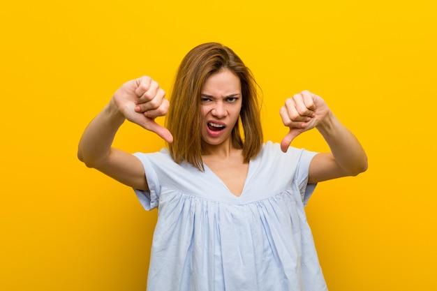Giovane donna abbastanza giovane che mostra pollice giù e che esprime avversione.
