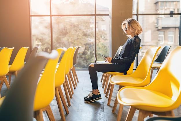 Giovane donna abbastanza impegnata seduta da sola nella sala conferenze