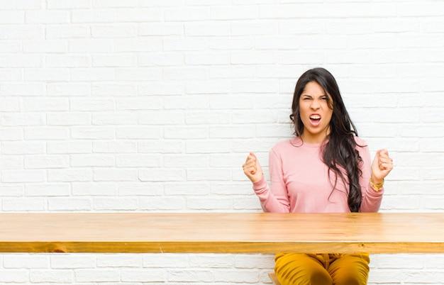 Giovane donna abbastanza latina che grida aggressivamente con un'espressione arrabbiata o con i pugni serrati per celebrare il successo