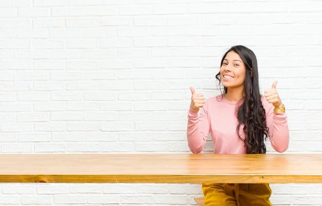 Giovane donna abbastanza latina che sorride ampiamente guardando felice, positivo, sicuro e di successo, con entrambi i pollici in su seduto di fronte a un tavolo