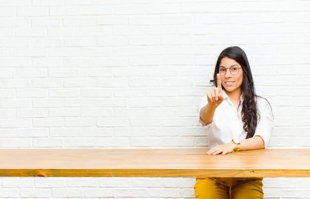 Giovane donna abbastanza latina che sorride con orgoglio e con fiducia facendo numero uno