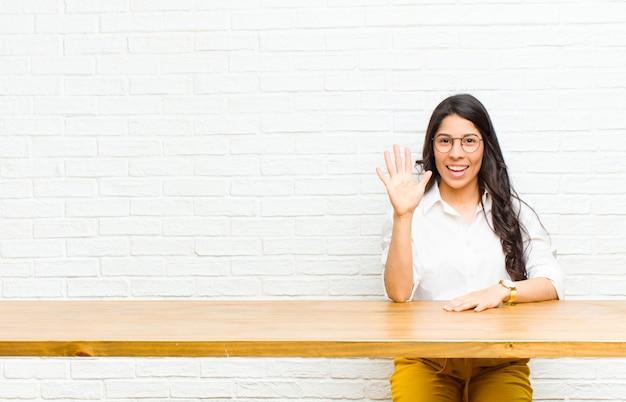Giovane donna abbastanza latina che sorride e che sembra amichevole, mostrando numero cinque o quinto con la mano in avanti, contando alla rovescia seduta davanti a un tavolo