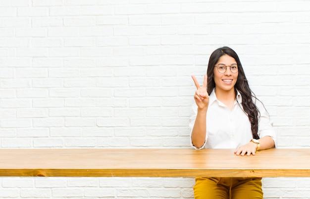 Giovane donna abbastanza latina che sorride e che sembra amichevole, mostrando numero due o secondi con la mano in avanti, contando alla rovescia seduta di fronte a un tavolo