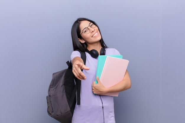 Giovane donna abbastanza latina dello studente contro la parete grigia