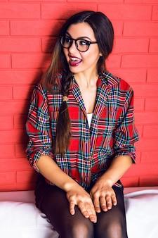 Giovane donna abbastanza seducente hipster con gambe lunghe divertendosi e seduto sul divano bianco, indossa una camicia a quadri e occhiali trasparenti, capelli lunghi e trucco luminoso.