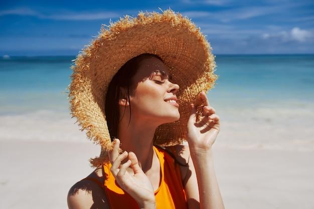 Giovane donna abbronzata in un cappello di paglia su uno sfondo del mare