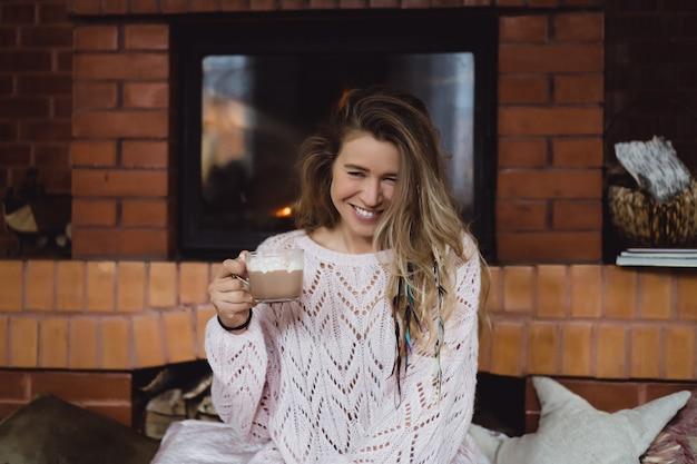 Giovane donna accanto al camino bevi cacao con marshmello con cane.