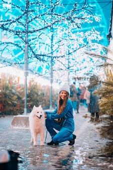 Giovane donna accovacciata accanto a un cane su una strada d'inverno