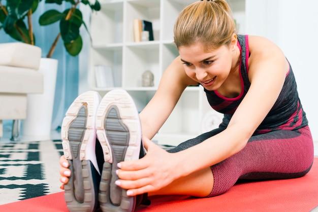 Giovane donna adatta a casa stretching e riscaldamento prima dell'allenamento