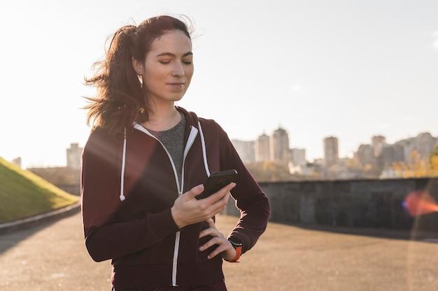 Giovane donna adatta che controlla il suo telefono