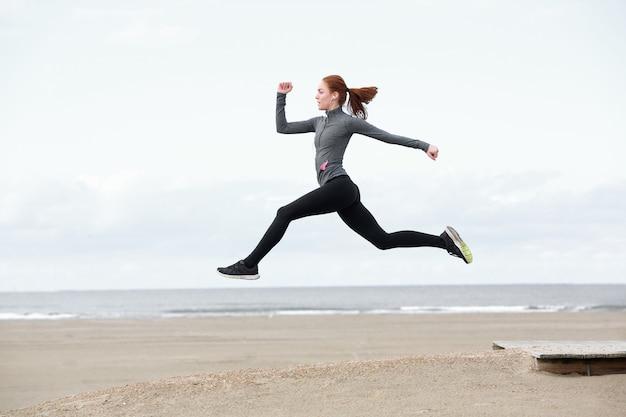 Giovane donna adatta che corre e che salta