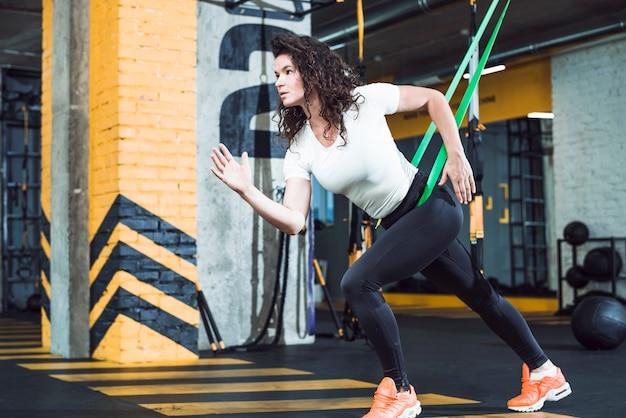 Giovane donna adatta che fa esercizio nel club di forma fisica