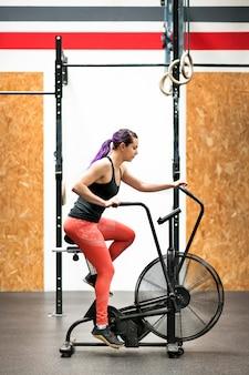 Giovane donna adatta che risolve su una cyclette