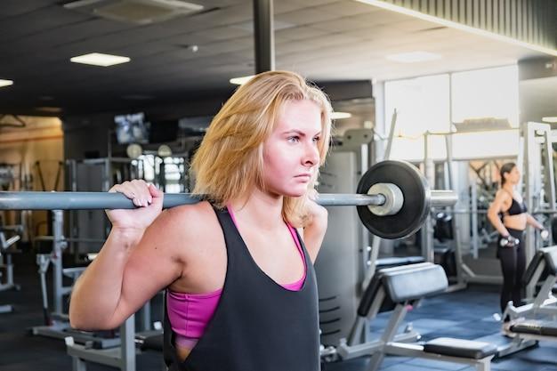 Giovane donna adatta in palestra facendo esercizio di sollevamento pesi. atleta femminile in una sala fitness che risolve con il bilanciere