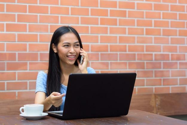 Giovane donna adolescente asiatica felice che parla al telefono mentre pensa