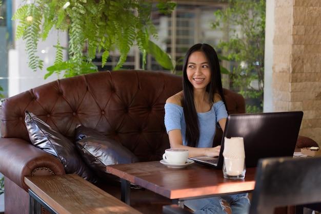 Giovane donna adolescente asiatica felice che sorride mentre pensa alla caffetteria all'aperto