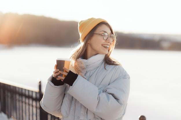 Giovane donna adolescente felice che tiene una tazza di caffè asportabile