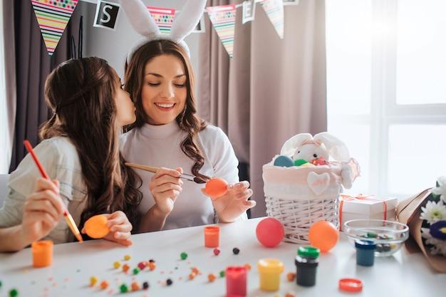 Giovane donna adorabile e ragazza che preparano per pasqua. figlia bacio madre dipingono le uova e si siedono al tavolo. colorato e festoso.