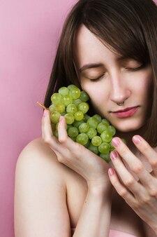 Giovane donna adulta con gli occhi chiusi tenendo l'uva in mano