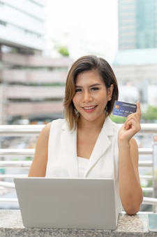 Giovane donna affascinante che mostra la carta di credito per il pagamento per la compera online con il computer portatile