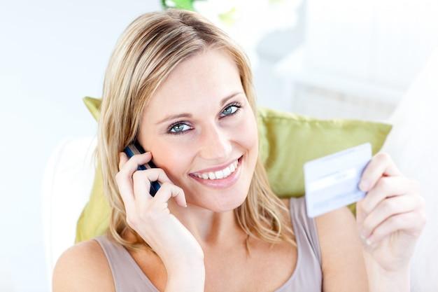 Giovane donna affascinante che parla sul telefono che tiene una carta