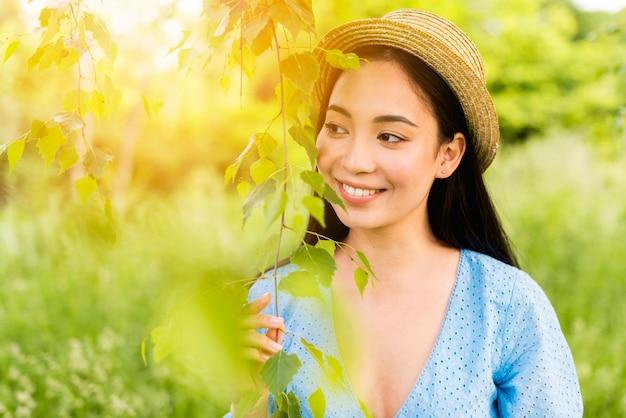 Giovane donna affascinante che sorride mentre appoggiandosi alle foglie in natura