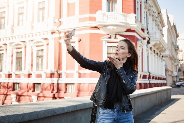Giovane donna affascinante che tiene smartphone, prendendo selfie pur essendo fuori, camminando in città e godendo la giornata calda