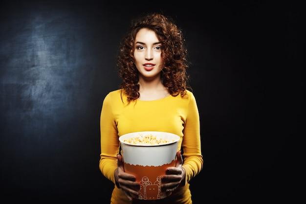 Giovane donna affascinante con il secchio del popcorn isolato sulla parete nera
