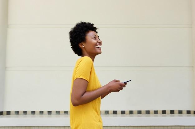 Giovane donna africana allegra che cammina con un telefono cellulare
