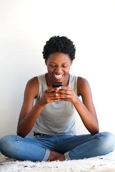 Giovane donna africana allegra che si siede e che utilizza telefono cellulare