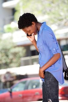 Giovane donna africana che parla sul telefono cellulare all'aperto e sorridente
