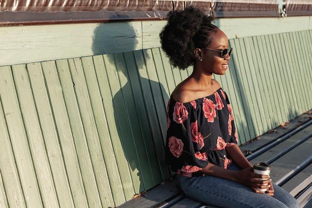 Giovane donna africana che si siede su una panchina