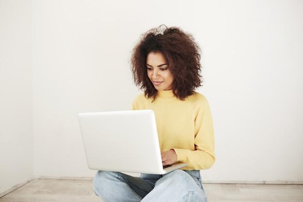 Giovane donna africana che sorride esaminando computer portatile che si siede sul pavimento