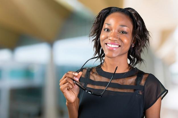 Giovane donna africana che tiene i suoi occhiali e sorridente