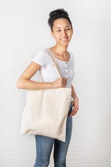 Giovane donna africana che tiene la borsa bianca di eco