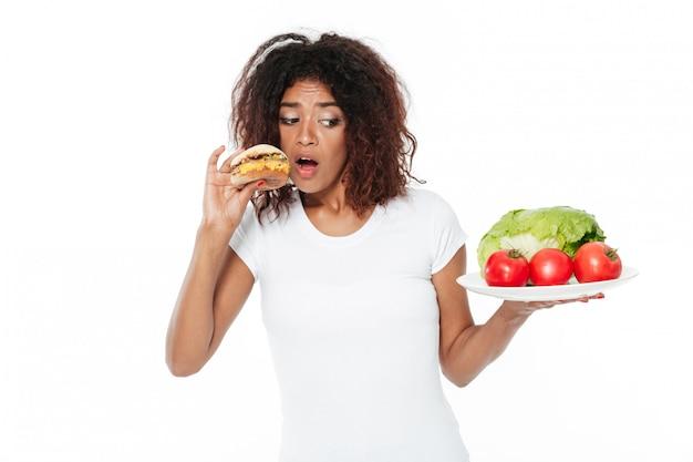 Giovane donna africana confusa che sceglie fra l'hamburger e le verdure.