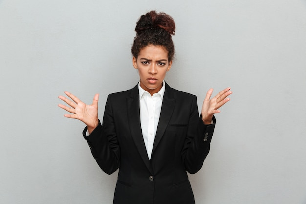 Giovane donna africana confusa di affari che controlla parete grigia