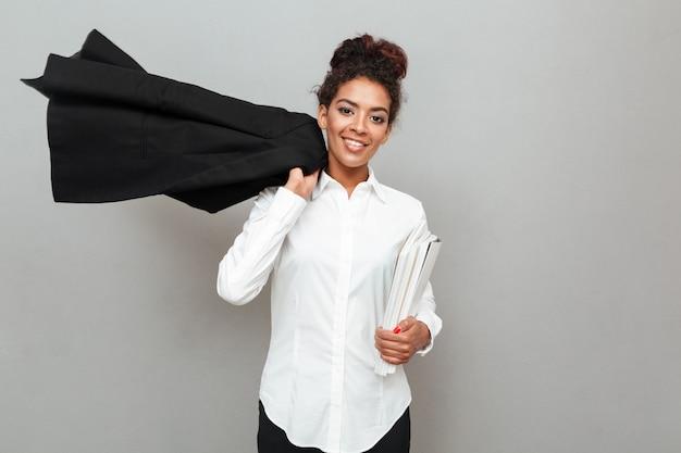 Giovane donna africana di affari che controlla parete grigia