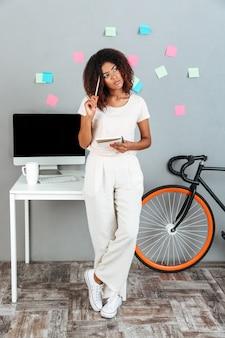 Giovane donna africana di pensiero che sta computer vicino