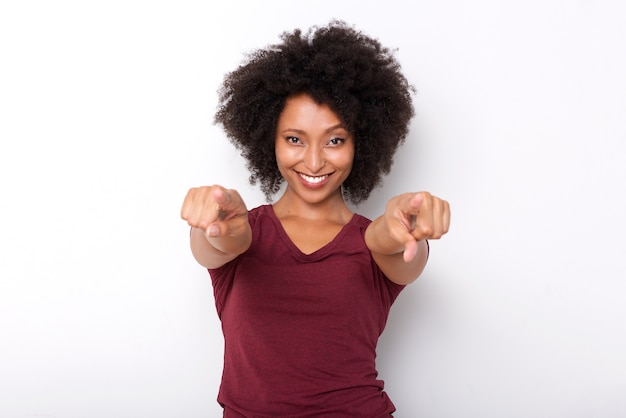 Giovane donna africana felice che indica entrambe le mani e che sorride sulla priorità bassa bianca