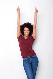 Giovane donna africana felice che indica le dita su nell'eccitazione su fondo bianco