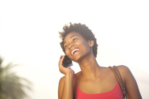 Giovane donna africana felice che parla sul telefono cellulare