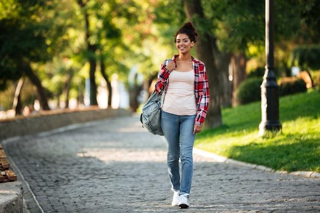 Giovane donna africana sorridente che cammina all'aperto