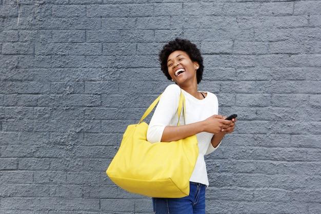 Giovane donna africana sorridente con il telefono cellulare che osserva via