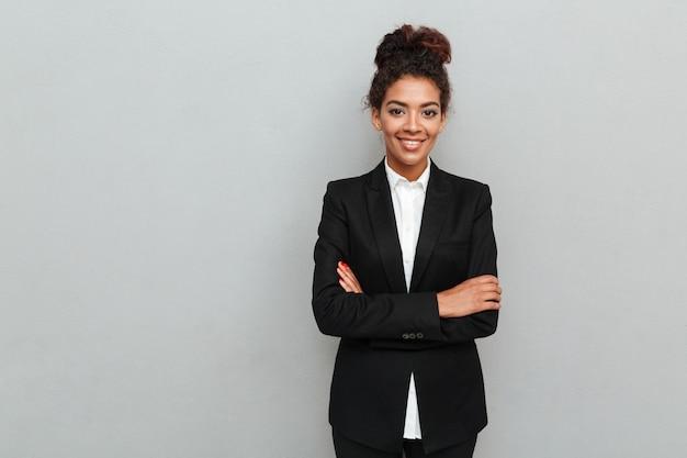 Giovane donna africana stupefacente di affari che controlla parete grigia