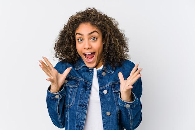 Giovane donna afro-americana che celebra una vittoria o un successo, è sorpreso e scioccato.