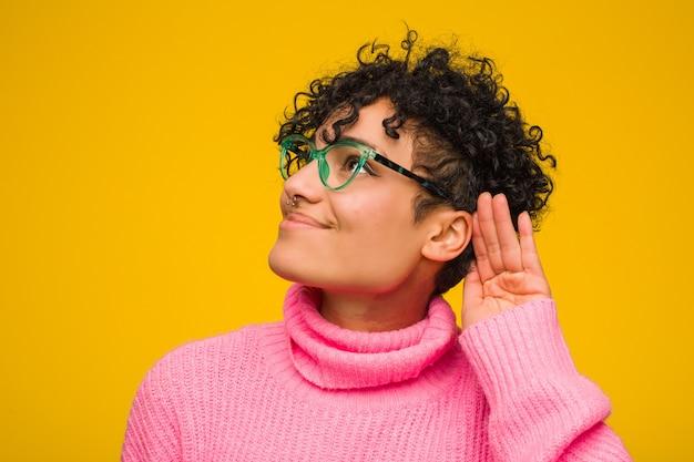 Giovane donna afro-americana che indossa un maglione rosa cercando di ascoltare un gossip.