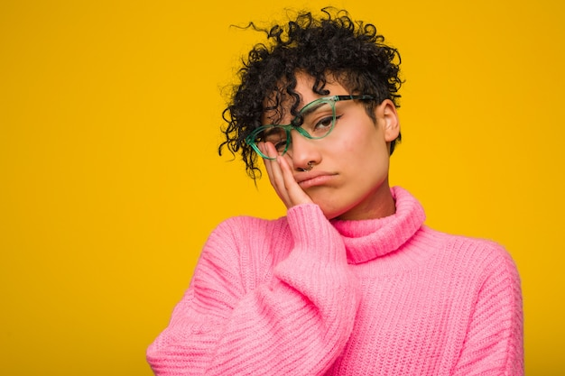 Giovane donna afro-americana che indossa un maglione rosa che è annoiato, affaticato e ha bisogno di una giornata di relax.