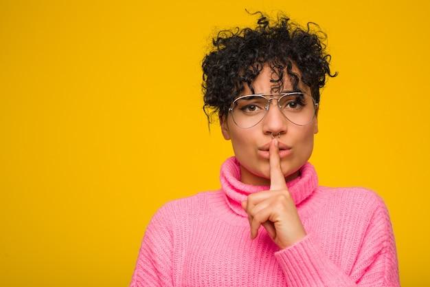 Giovane donna afro-americana che indossa un maglione rosa mantenendo un segreto o chiedendo silenzio.